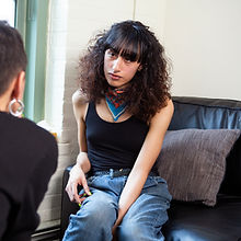 A transgender woman sitting on a therapi