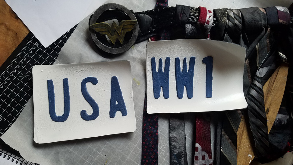Belt Buckle: Did some weathering to the buckle with black paint and a mix of black/yellow acrylics.   License Plates: Mixed a dark and light blue to achieve a color close to that seen on licence plates. Hand painted the letters.
