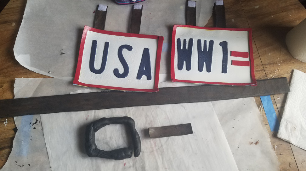 """Used contact cement to glue one side of the leathers to the licence plate, then added velcro to the other half so I could take them on and off with ease.   I also finished painting the extra decorative part of the WW1 licence plate (the lines) and attached with contact cement.   The long leather strip was painted with my usual leather painting technique.   The """"handle"""" is what I will attach to the tie belt so I have something that can secure the chains. It too was made out of scrap worbla, and primed with wood glue."""