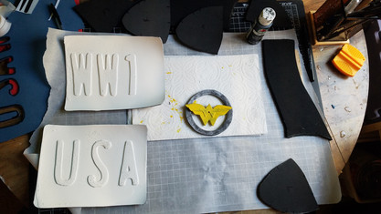 Belt Buckle: Added weathering to the silver part and added more layers of yellow to the Wonder Woman logo.   License Plates: I primed with white plastidip, unfortunetly I was rushing it so I sprayed on layers that were too thick, and I KNEW it would do this but I went ahead and did it anyway. It caused bubbling effect so I tried to just keep spraying more layers of white paint over it. Now the paint cracks a bit easily, but I'm learning from my mistake and chalking it up to post apocalyptic damage.