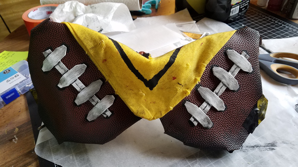 The finished football boobs.   I added some black paint to the edges to further the dirty look, and it's not pictured but I attached the belts and some caution tape around the sides to hide the straps, and blackened/aged those as well.   The bandana I ripped in a few places, used a wire brush to scratch the holes out a bit. Added some very light strokes of black paint, a few blood splatters, ET VOILA!