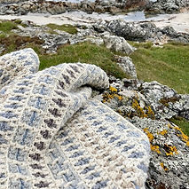 The tapestry Daisy Sampler pattern, on the rocks of Hynish on Tiree