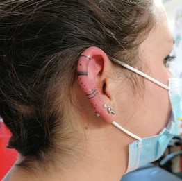 Handpoked pattern ear tattoo