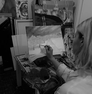 Luna Smith painting a Scottish landscape in her studio.