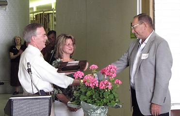 Bill Boyle and Lori Weston give plaque to Richard Stigliano