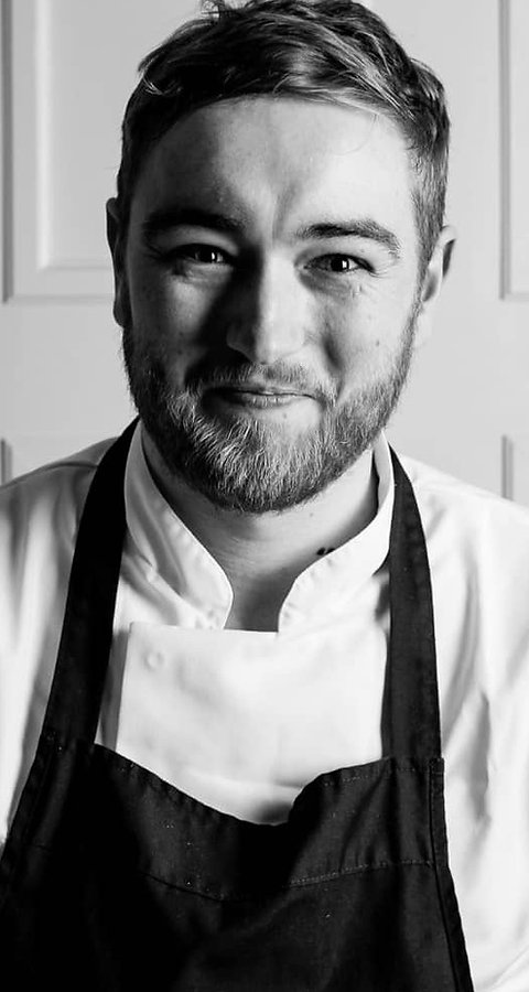 A black and white photo of Christopher Greenacre stood smiling in chef whites