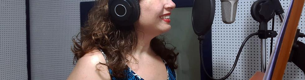 Fotografia de uma mulher, visível do nariz até os ombros, dentro de um estúdio de locução. Ela é branca, tem cabelos ondulados na altura dos ombros, veste uma blusa regata e fone de ouvido. Ela está sorrindo em direção ao microfone, à direita da imagem, um equipamento próprio para locução com tela de proteção anti-ruido que o separa da mulher.