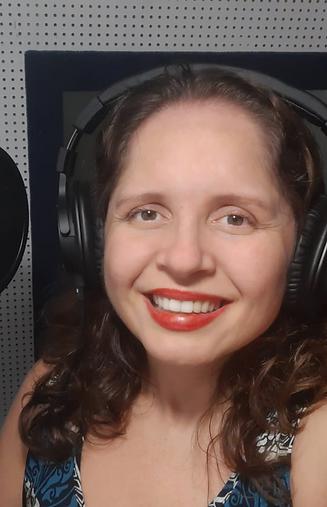 Fotografia da locutora Samara Souza. Uma mulher branca, com cabelo castanho na altura dos ombros e olhos castanhos. Samara está sorridente, usando um fone de ouvido próprio para locução.