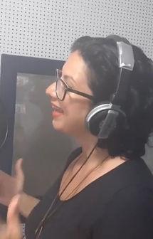 Fotografia de uma mulher falando, virada para a esquerda, de óculos de grau e vestindo um microfone.