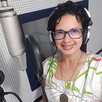 Fotografia da locutora Bianca Oliveira. Uma mulher branca, de cabelos encaracolados curtos e pretos, usando óculos de grau com armação preta e uma blusa branca estampada. Bianca está sorridente, usando um fone de ouvido próprio para locução, e posiciona-se ao lado de um microfone, também próprio, dentro do estúdio.