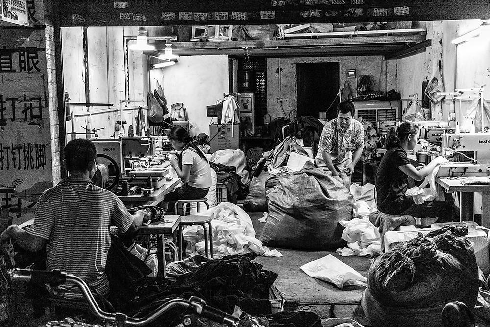Family working tirelessly in a garage sweat-shop.