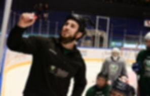 En tränare som ritar på en tavla inför en grupp på Färjestad CCM Hockey Camp.