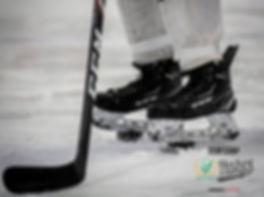 Skridskorna av en hockeyspleare som står på puckar.