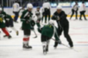 En tränare som hjälper en hockeyspelare på Färjestad CCM Hockey camp.