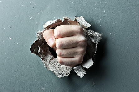a wall is broken through by a fist.jpg