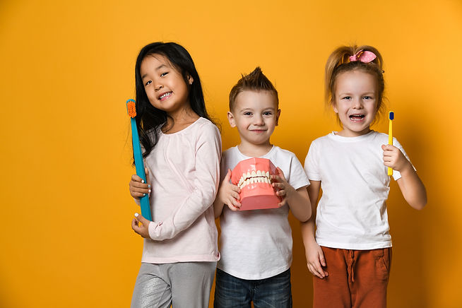 Three children with toothbrushes and a D