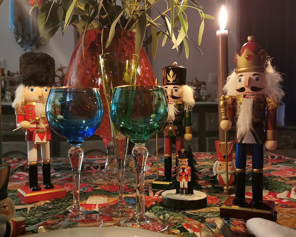 Une table dressée de Noël avec des verres anciens et accompagnée par des casse-noisette