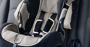 A child's car-seat against a black background.