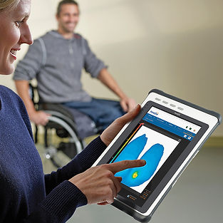 A physical therapist monitors a patient's skin with XSENSOR's ForeSite SS Seat System as the patient sits in a wheelchair.