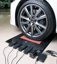 A vehicle's front-driver's wheel is parked on an XSENSOR IX500-series high-resolution tire testing sensor.