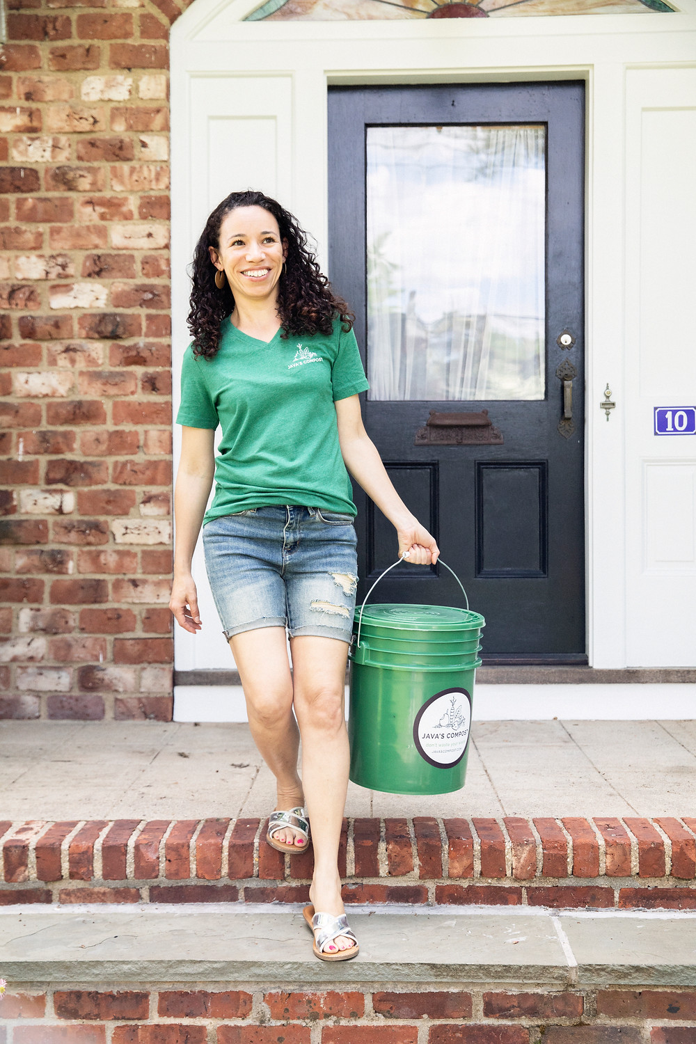 Michelle carrying a compost bucket from someone's house