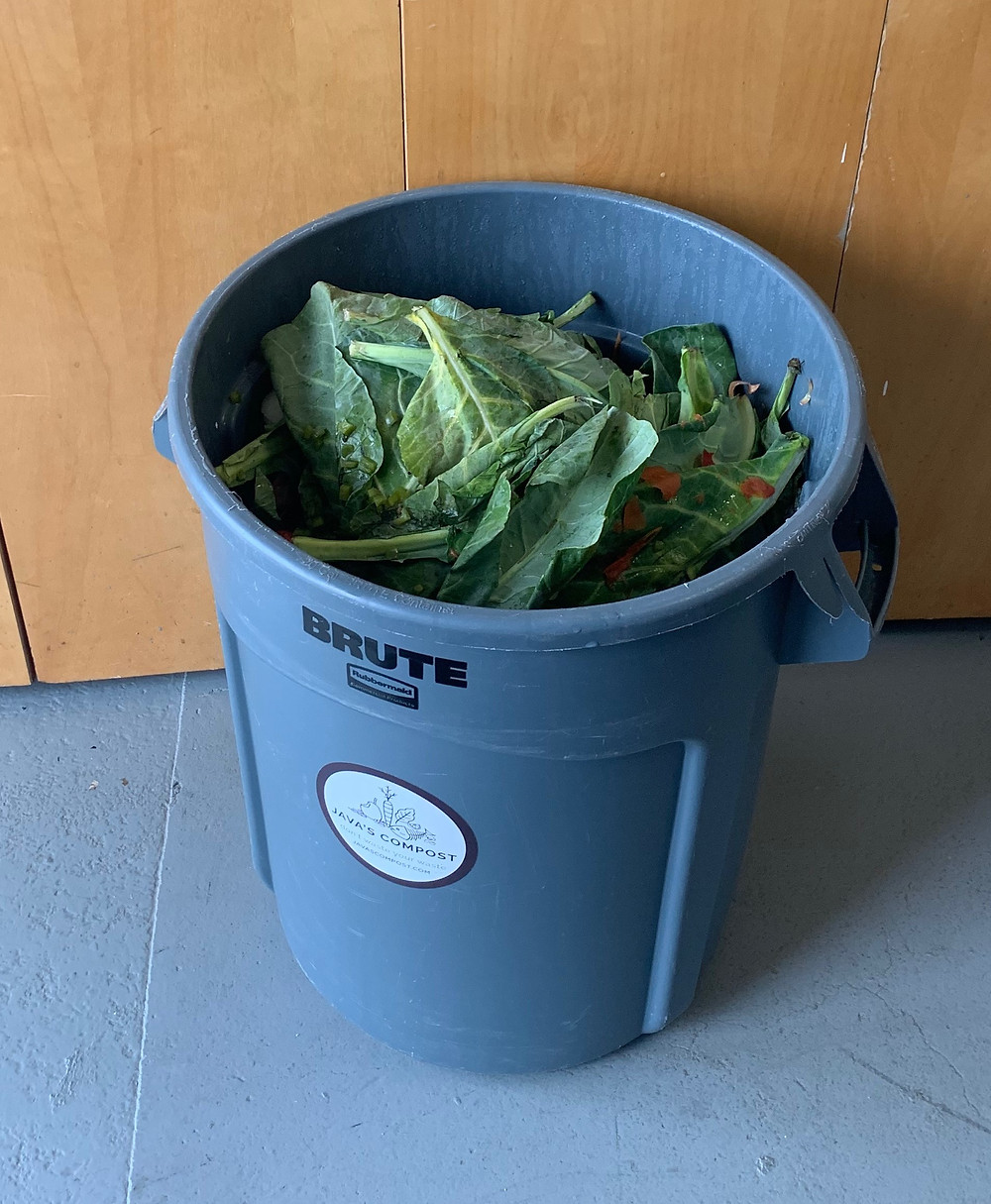 A giant garbage can full of compostable waste