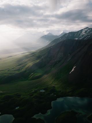 Rays of light illuminate the mountains surrounding Lenin Peak (Matt Horspool)