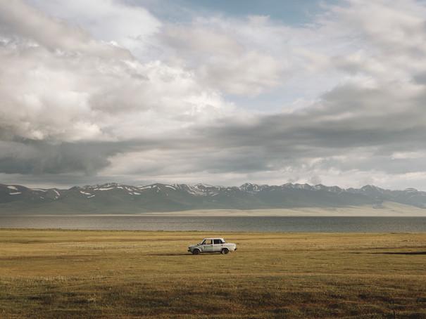 A lone Lada Niva sits along the banks of Song Kul Lake.