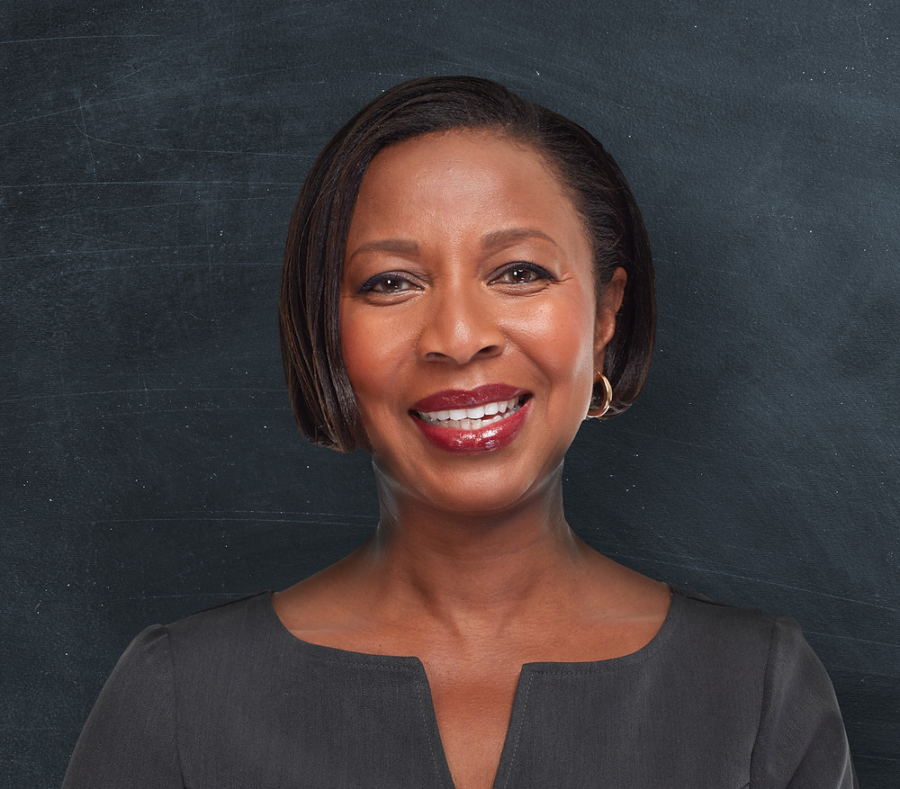 This is a portrait of a Black woman standing against a black chalkboard background. She has short, straight black hair, gold hoop earrings, and dark red lipstick. She's smiling, and she's wearing a fancy black top.