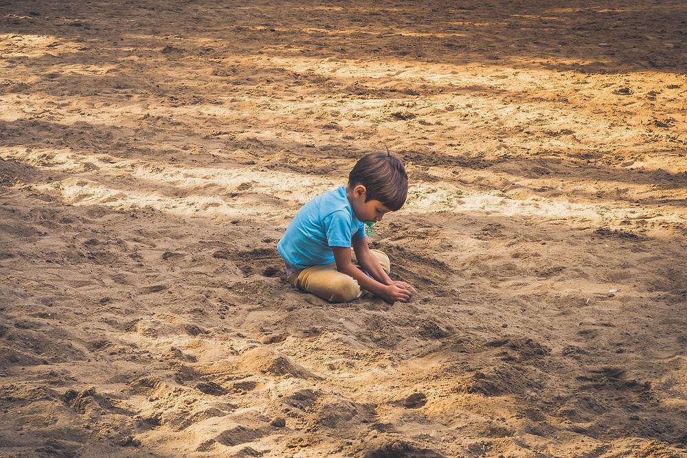 Menino brinca em tanque de areia