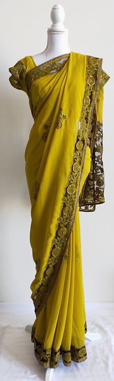 Lovely mustard yellow sari with heavy green and gold net border design