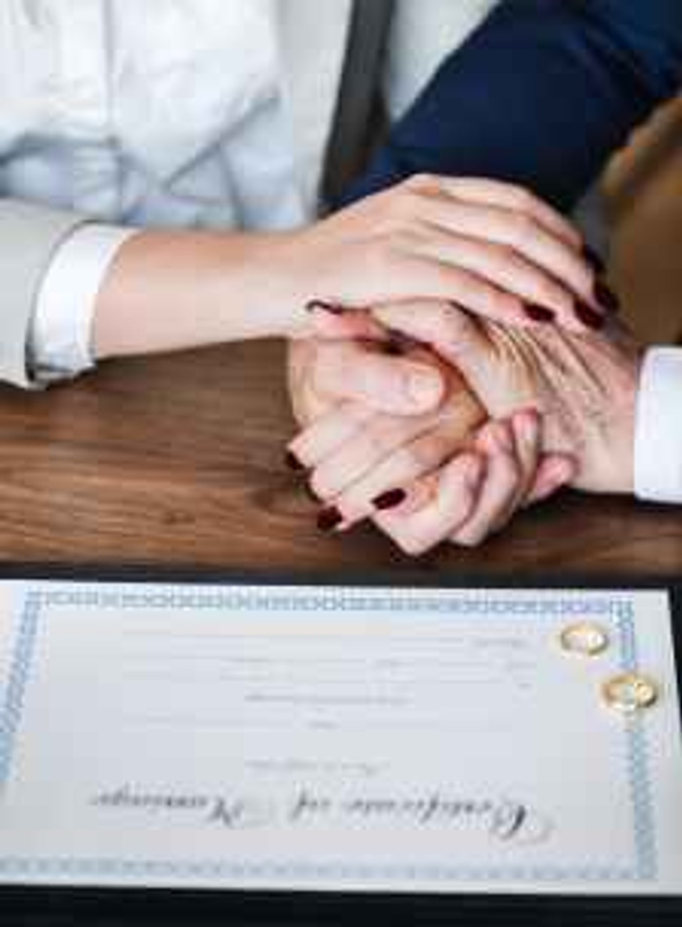 man and woman holding hands on brown wooden table