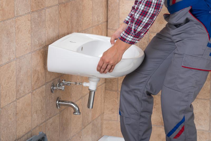 Handyman Installing Sink In Bathroom