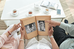 family going through photo album while having tea