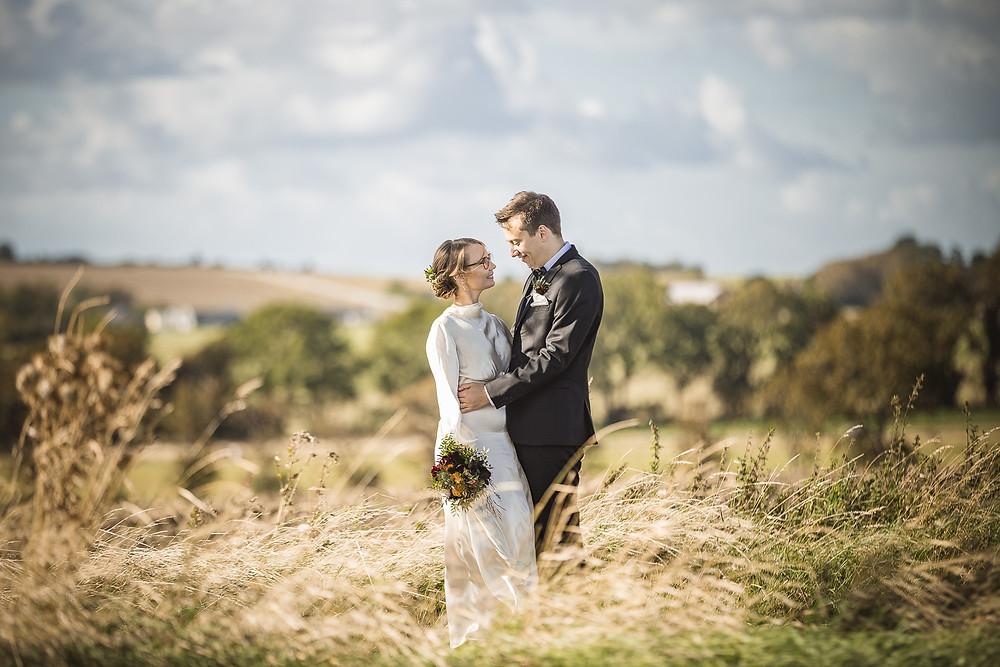 Romantiskt bröllopsporträtt i motljus med utsikt över ängar