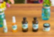 moisture serum, golden oil, oil cleanser, tonic and wonder balm bottles with jars of flowers