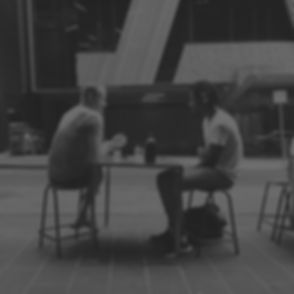 photo-of-two-men-talking-while-sitting-o