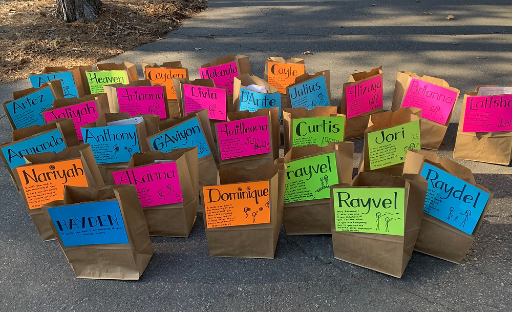 Approximately twenty paper grocery bags with individualized neon labels with names