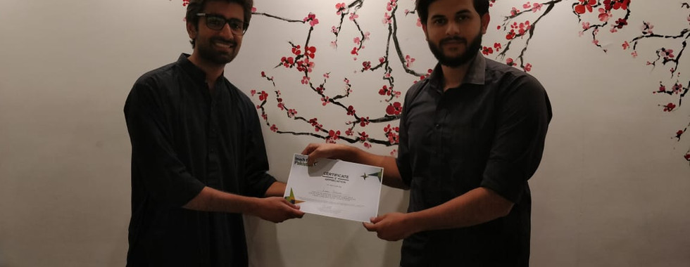 Zain Maken, Manager Training and Development handing over the certificate of appreciation to one of our campus ambassadors.