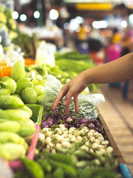 Des légumes frais dans un marché de producteurs locaux. Les étales sont garnies de différents légumes comme des courgettes, concombres, salades, poivrons, aubergines, carottes. Les légumes sont de qualité et présentent un aspect sain. Une personne en premier plan se sert en légumes frais.