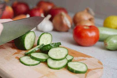 crudités (service de livraison quotidienne) lavés et découpés à la main sur une planche à découper en bois. Les légumes sont découpés en rondelles (tomate, courgette, oignon, ail).