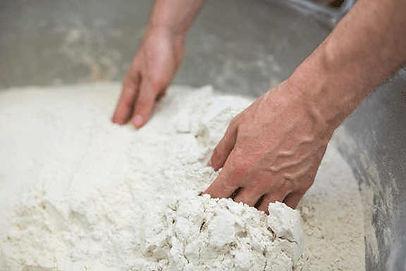 Farine à pizza italienne pétrie à la main. Entre dans la composition d'une recette de pâte à pizza avec peu de levure et des temps de pause importants pour garantir la saveur et une bonne digestion.