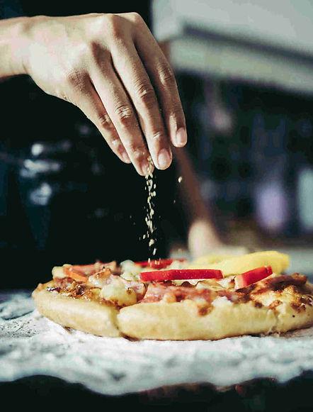 Préparation d'une pizza tartiflette à base de crème avec des ingrédients de qualité (tomate, pomme de terre, lardons, reblochon, emmental, mozzarella), selon le label qualité pizza agde. La pizza présente une pate fine avec des bords généreux. Il s'agit d'une pizza artisanale.