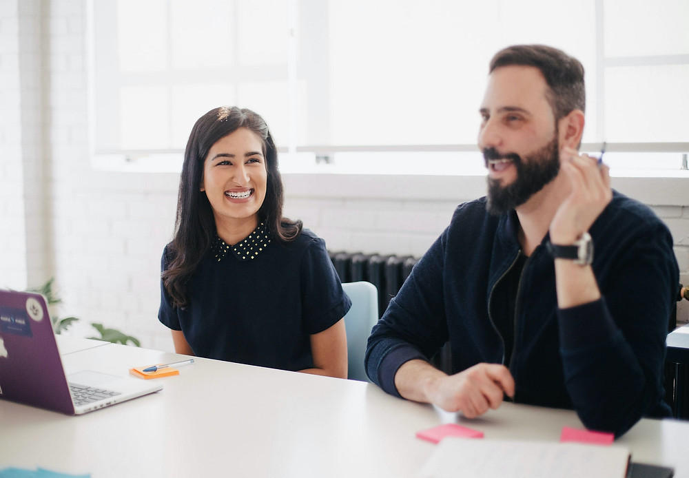 Two smiling marketers sit at a desk