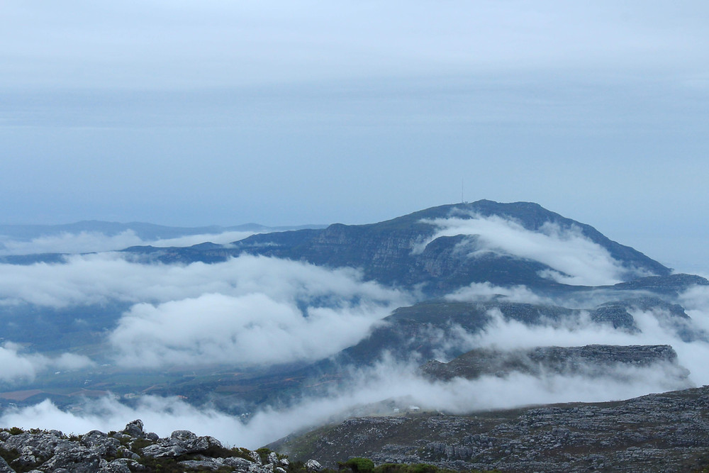 Constantiaberg peeking above the low clouds viewed from Maclear's Beacon on Table Mountain..