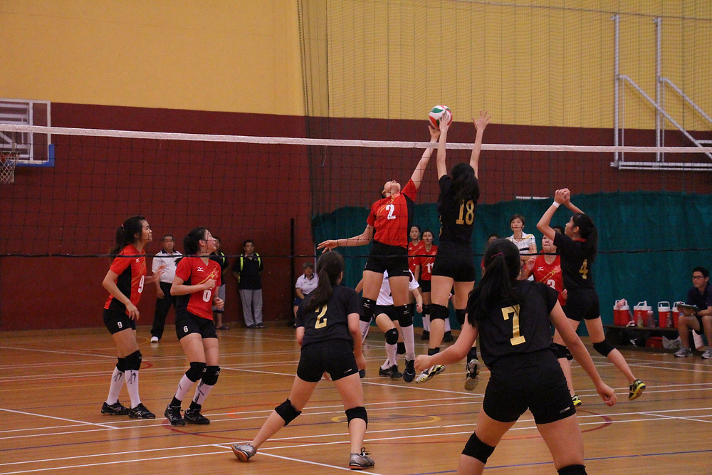 The stand-off between Hwa Chong Junior College's Center Player No. 2 and Victoria Junior College's Center Blocker No. 18. HCJC Center Player sends a spike across, only to be met with her rivalry who jumped and made an attempt to block off the attack. (Photo credit: Goh Shu Hui Gina)