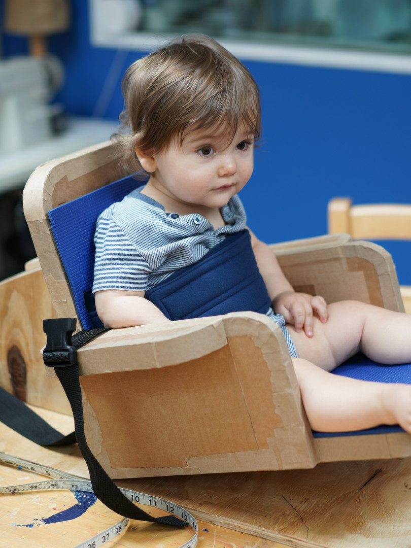 A toddler with bare feet sits in a cardboard chair mounted to a wooden platform.  The seat surface and backrest are lined with a blue yoga mat and are tilted back about 30 degrees relative to the platform. The chair has two armrests, one on each side. A wide blue belt wraps around his torso.