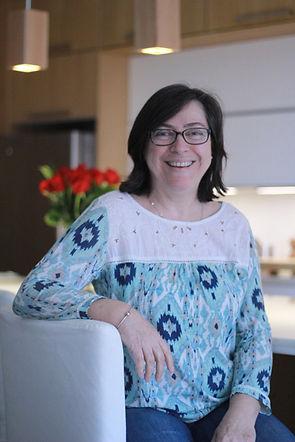 Heloisa Braga, owner of Arrange my Space sitting in the minimalist kitchen