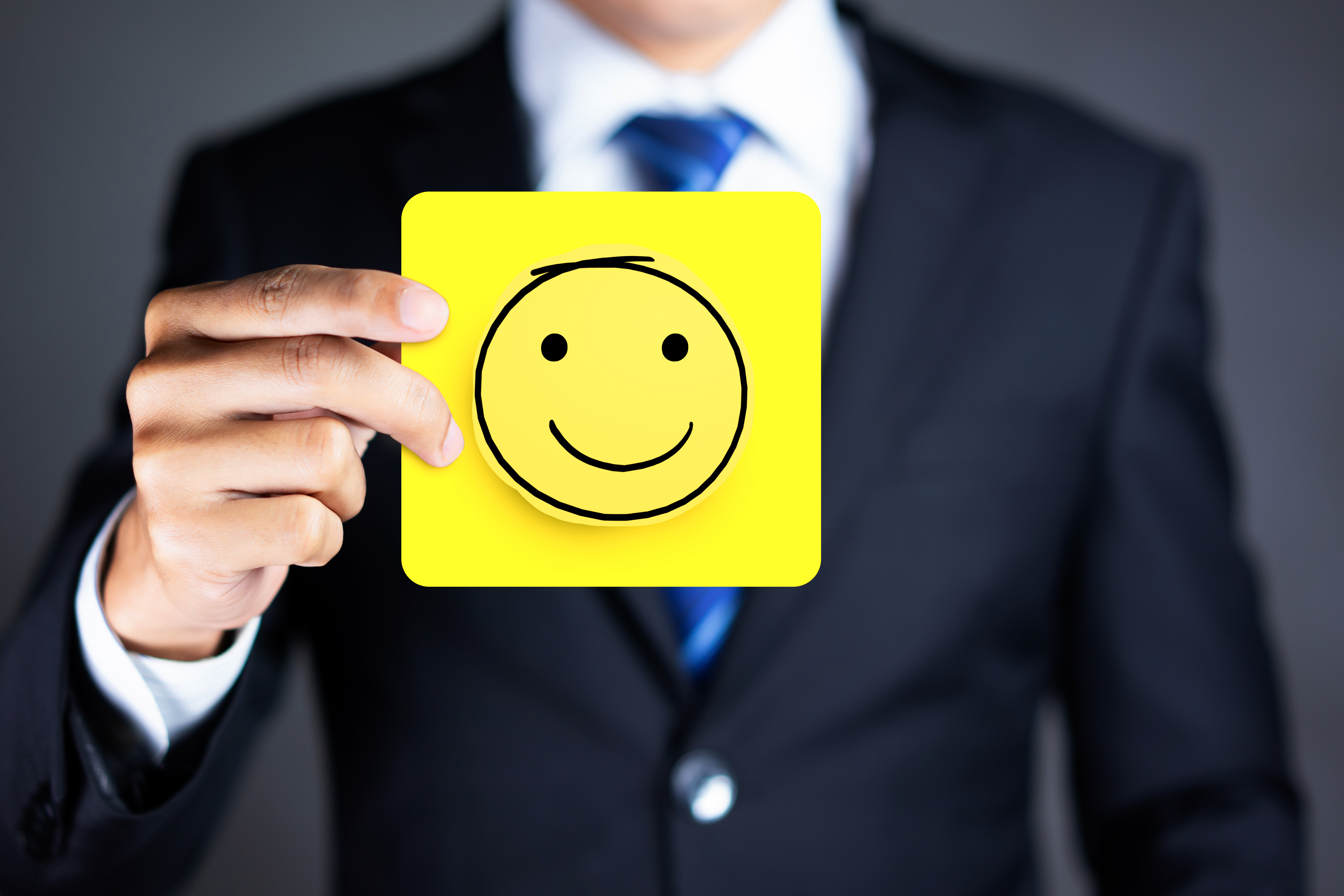 Businessman hold a happy face icon drawn