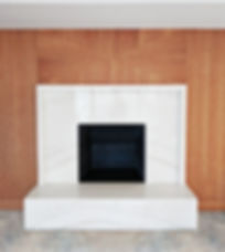 Modern onyx fireplace with wooden wall paneling in a luxury New Jersey home designed by Lenart Architecture.